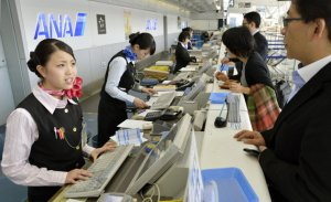 Employees deal with passengers at the counter at Sendai Airport in Sendai, northern Japan after flights in and out of the airport were canceled Tuesday-nader-nazemi-